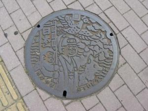 Okayama manhole cover featuring Momotaro, the Peach Boy