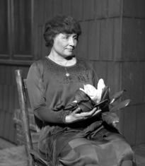Helen Keller sitting holding a magnolia flower, circa 1920 (Presumed Public Domain, from Los Angeles Times photographic archive, UCLA Library)